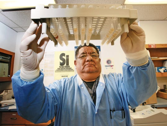 Senior microbiologist Sergio Mendez examines tubes that will be tested for sexually transmitted infections.