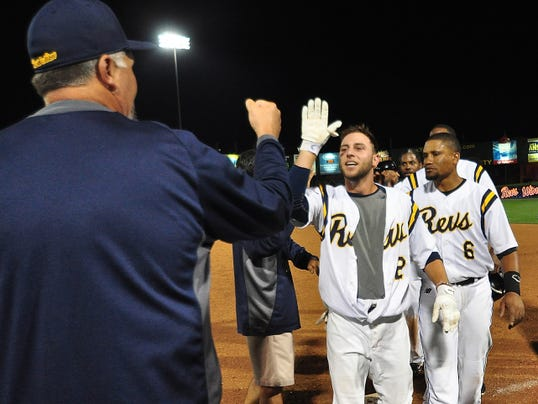 Mikey Reynolds gets a high five from Manager Mark Mason after Reynolds' walk-off hit allowed the winning run to score on Monday night in an 8-7 win over the Lancaster Barnstormers.