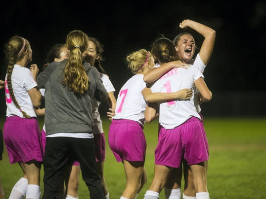 Fairfield girls' soccer players celebrate a 3-2 victory against York Catholic in a late-season matchup between two YAIAA Division III foes. Fairfield's win allowed the Green Knights to move into a first-place tie with the Irish.