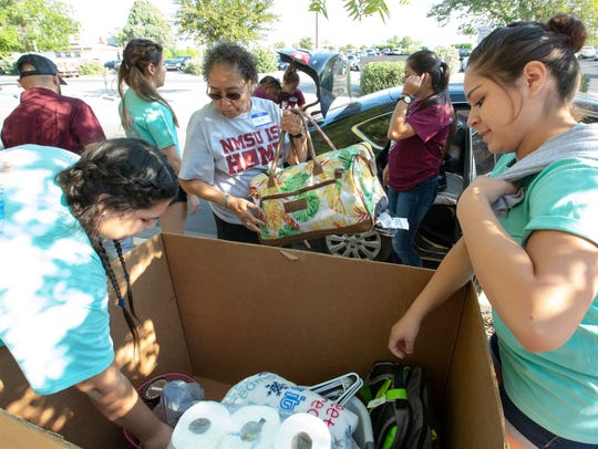 Volunteers Ashley Perez, 19, left, Paula Garcia, center, and Natalia Molina help freshmen move into Garcia Hall on Saturday, August 11, 2018 at New Mexico State University.