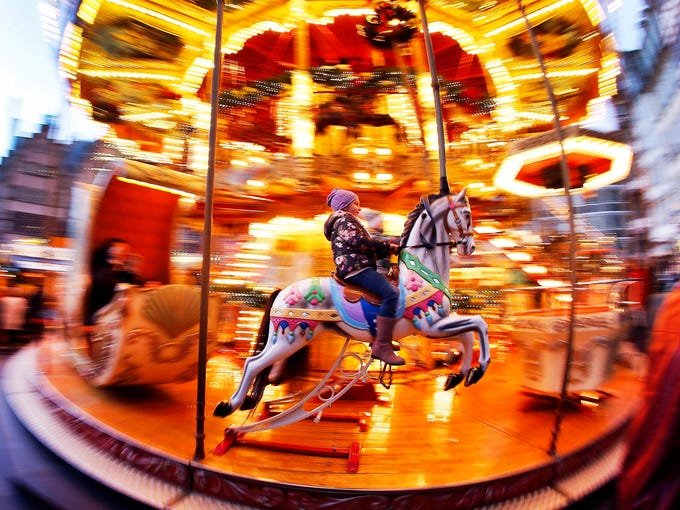 A girl rides a horse on a merry-go-round on the Christmas