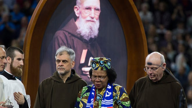 Capuchin friars escort Paula Medina Zarate of Panamá during a Nov. 18, 2017, ceremony in Detroit that celebrates the beatification of Father Solanus Casey. Zarate's skin disease was healed after she prayed at Casey's tomb, and the Vatican agreed that a miracle had occurred.