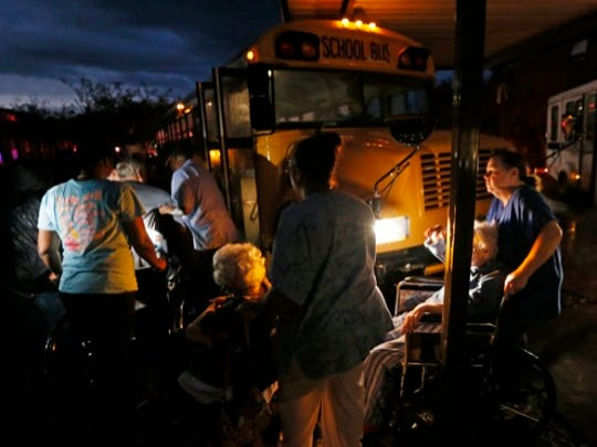 Nursing home personnel assist residents as they are wheeled to a waiting bus outside a Louisville, Miss., nursing home, Monday, April 28, 2014 after the facility and the Winston Medical Center next door were heavily damaged by a tornado. Tornados flattened homes and businesses, flipped trucks over on highways and injured numerous  people in Mississippi and Alabama on Monday as a massive, dangerous storm system passed over several states in the South, threatening additional twisters as well as severe thunderstorms, damaging hail and flash floods.