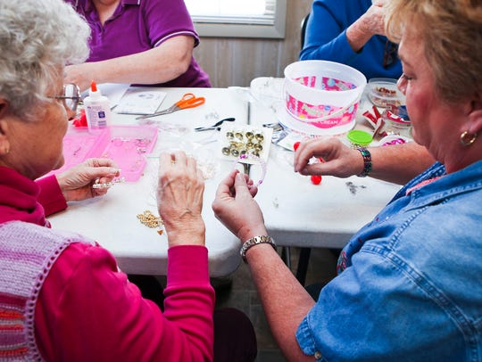 Ann Black, left, and Vivian Carros work on crafts at