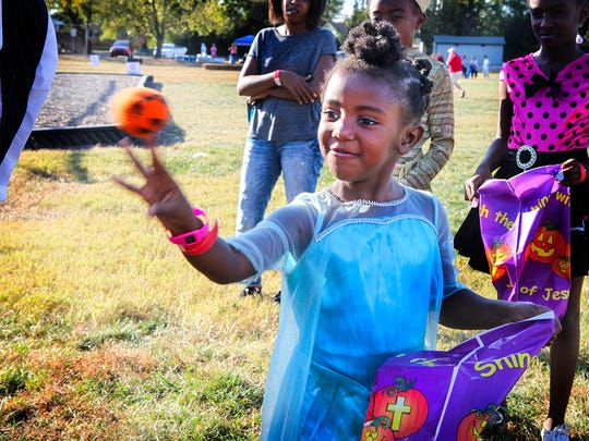 Makayla Hickerson, 5-year-old daughter of Tequoria Pigg, participates in a bean bag toss game at Reeves-Rogers Elementary's inaugural fall fest.