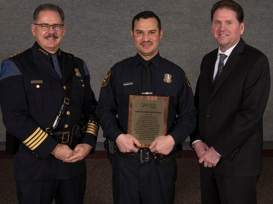Farmington Hills Officer of the Year Larry Hernandez (center) is flanked by Police Chief Chuck Nebus (left) and City Manager Dave Boyer.