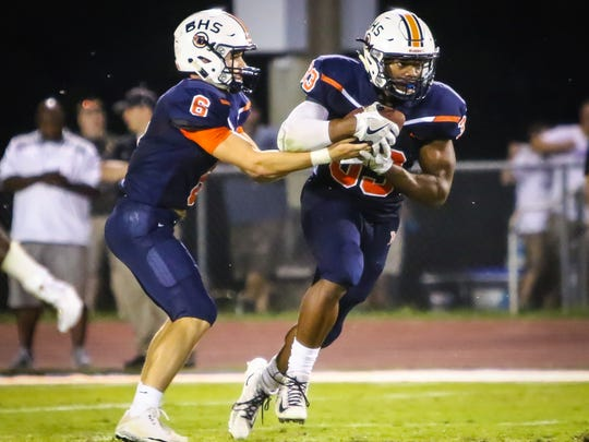 Blackman's Master Teague gets the ball from Connor Mitchell on Aug. 18, 2017,  against Hendersonville.
