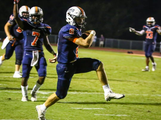 Blackman quarterback Conner Mitchell high steps into the end zone on Friday night against Hendersonville.