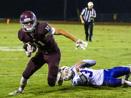 Eagleville's Graham Hatcher (11) slips past a Forrest defender during Friday's 21-20 Eagles win.