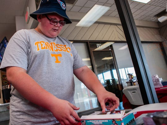 Logan Cantrell, 12, of McMinnville, looks over a box of collectible cards at Grand Slam Collectibles in Murfreesboro.