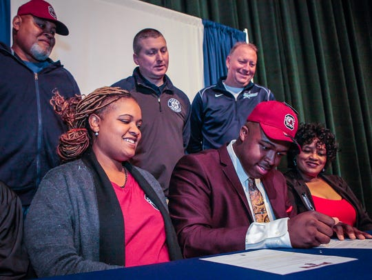 Siegel's Maxwell Iyama signed with South Carolina Wednesday, surrounded by family, coaches and friends, including (front row) sister Jaliyah Iyama, mother Heather Iyama and grandmother Deborah Bohanon and (back row) grandfather Billy Bohannon, Coach Michael Copley and Siegel principal Larry Creasy.