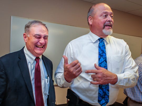 Bill Spurlock, right, jokes with recently retired county schools director Don Odom during a June 19 reception in Odom's honor.