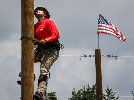 A lineman climbs a utility pole during a competition in Murfreesboro.