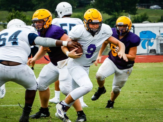 Smyrna quarterback Alex Bannister eyes running room en route to a TD run during Friday's scrimmage against Centennial.