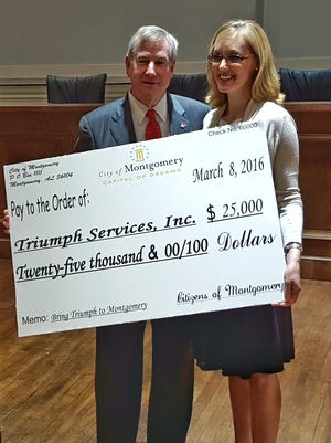 Mayor Todd Strange presents Triumph Services founder Brooke Bowles with a ceremonial check for $25,000 Tuesday, March 15.