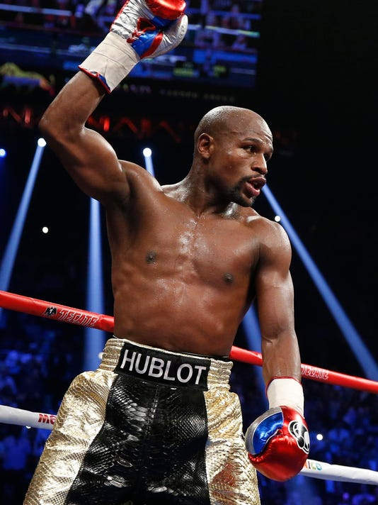 FILE - In this May 2, 2015, file photo, Floyd Mayweather Jr. celebrates during his welterweight title fight against Manny Pacquiao, in Las Vegas. Conor McGregor has come to an agreement with UFC that has moved a proposed fight with Floyd Mayweather Jr. closer to reality. (AP Photo/John Locher, File)