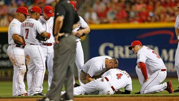 Reds second baseman Brandon Phillips (4) is attended to after injuring his thumb Wednesday night.