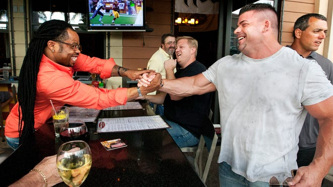 Quincy Sorrell, left, greets Steve Gorrie during a recent reunion of the 2004 Florida Firecats at House of Brewz at the Gulf Coast Town Center. Ten years ago, the Firecats won the ArenaCup of the now-defunct arenafootball2 league.