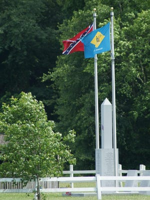 A Confederate flag and Delaware state flag fly at the Delaware Confederate Monument in Georgetown on Wednesday. A national debate about the secessionist battle flag has reignited following the shooting of nine at a historic black church in downtown Charleston, South Carolina.