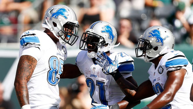 Eric Ebron #85 celebrates with  Reggie Bush #21 and  Jeremy Ross #12 of the Detroit Lions after his touchdown in the second quarter against the New York Jets at MetLife Stadium on September 28, 2014 in East Rutherford, New Jersey.