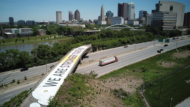"Artist Mandi Caskey and friends created a ""We are stronger together"" mural with a COVID-19 message on the Whittier Street overpass. The road has been abandoned for years. It is over Interstates 70 and 71 on the southwest side of downtown Columbus."