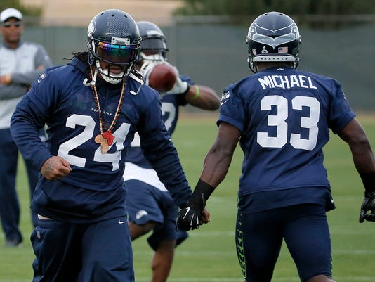 Seattle Seahawks' Marshawn Lynch (24) low-fives teammate Christine Michael (33) as they run drills during a team practice for NFL Super Bowl XLIX football game, Wednesday, Jan. 28, 2015, in Tempe, Ariz. The Seahawks play the New England Patriots in Super Bowl XLIX on Sunday, Feb. 1, 2015. (AP Photo/Matt York)