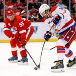 Detroit Red Wings defenseman Niklas Kronwall (55) puts his stick on a Washington Capitals left wing Alex Ovechkin (8) shot in the first period of an NHL hockey game in Detroit Sunday, April 5, 2015.