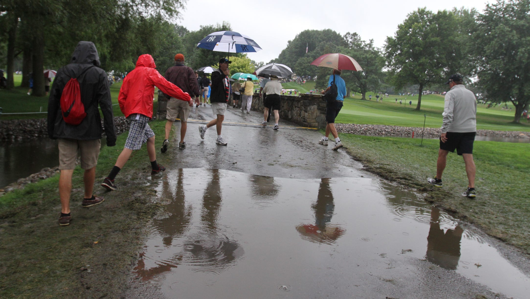 Fans try to avoid a large puddle between the 1 and 13 fairways during the second round at the  95th PGA Championship held at Oak HIll Country Club in Pittsford on August 9, 2013.