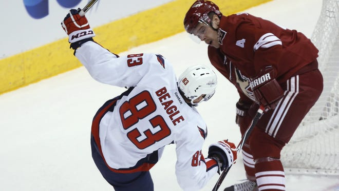 Arizona Coyotes defender Zbynek Michalek checks Washington Capitals forward Jay Beagle during the first period of an NHL hockey game Tuesday, Nov. 18, 2014, in Glendale, Ariz.