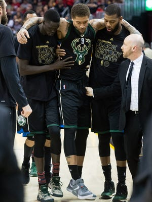 Bucks forward Michael Beasley (center) is helped off the court by teammates Thon Maker (left) and Greg Monroe after Beasley injured his knee vs. the Cavaliers on Monday night.