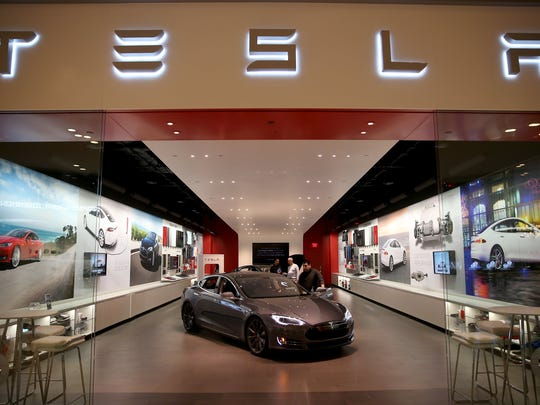 People look at a Tesla Motors vehicle on the showroom floor at a Florida mall. Both houses of the Michigan legislature passed a bill that would require all automakers, including Tesla, to sell through franchised dealers.
