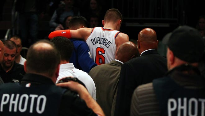 New York Knicks center Kristaps Porzingis (6) is helped off the court after being injured against Miami Heat during the first half at Madison Square Garden.
