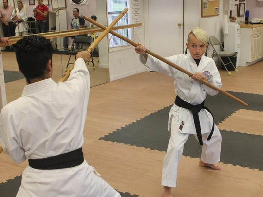 Bryant Martinez and Chase Polley demonstrate technique in the kobudo discipline.