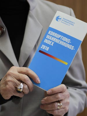 Edda Mueller, chairwoman of Transparency International Germany e.V., poses for the media with the Corruption Perceptions Index 2018 prior to the presentation of the yearly report at a news conference in Berlin, Germany, Jan. 29, 2019. The flyer reading: 'Corruption Perceptions Index 2018'.
