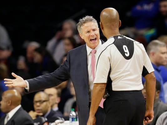 Philadelphia 76ers head coach Brett Brown disputes a call with referee Derrick Stafford (9) during the first half of an NBA basketball game against the Detroit Pistons, Wednesday, Jan. 27, 2016 in Auburn Hills, Mich. (AP Photo/Carlos Osorio)