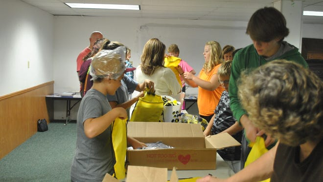 """Youth group members and leaders from the Bunker Hill Baptist Church fill hundreds of """"Bee Strong"""" bags for chemo patients at the Butler Library over the summer."""