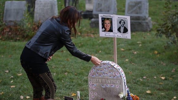 """Jillian Paris places an """"I Voted"""" sticker on the headstone"""