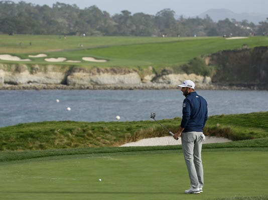 Dustin Johnson stands on the 17th green of the Pebble Beach Golf Links after missing a birdie putt during the final round of the AT&T Pebble Beach National Pro-Am golf tournament Sunday, Feb. 11, 2018, in Pebble Beach, Calif. (AP Photo/Eric Risberg)