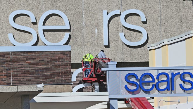Workers take the A out of the sign above the Sears entrance as they remove the name from the building.