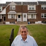 Myles Griffin, 74, poses in front of his home in Philadelphia. Griffin and his wife have lived 40 years in their three-bedroom row home and after retiring three years ago. The couple signed up for a reverse mortgage in May.