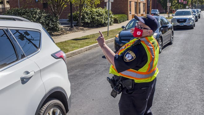 Bradley University police officer Nora Fales sends arrivals on their way on West Bradley Avenue on the first official move-in day for students Friday, August 21, 2020 in Peoria.