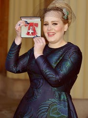 Adele holds her medal after being appointed a Member of the Order of the British Empire (MBE) for services to music. Prince Charles presented the award to her in 2013.