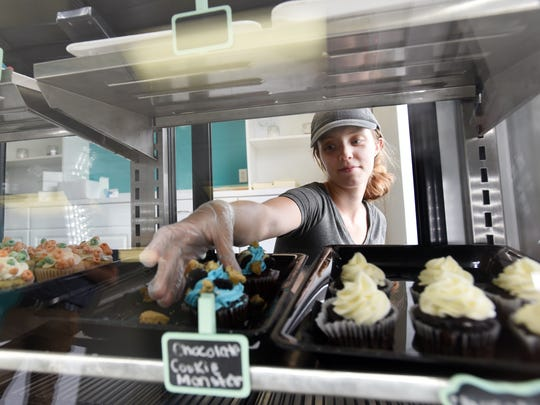 Linda Sprankle reaches for a chocolate cookie monster cupcake at Linda's Sweets on Linden Avenue in Zanesville.