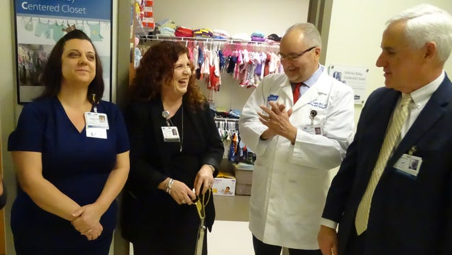 Donna Collier-Stepp laughs while chatting after cutting the ribbon for the new Adena Baby Centered Closet. Collier-Stepp helps lead Adena Health System's recovery program for pregnant women battling opiate addiction. Also pictured is Nurse Peggie Marcum, Dr. Ronald Lopez, and Adena CEO Jeff Graham.