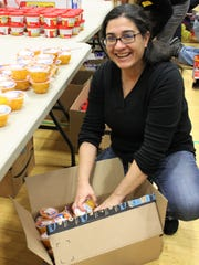 Josephine Ferrigno-Stack, parent of three Westfield Public Schools students and co-chair of the districtwide Community Service Day on March 27, helps unpack food items at Roosevelt Intermediate School.