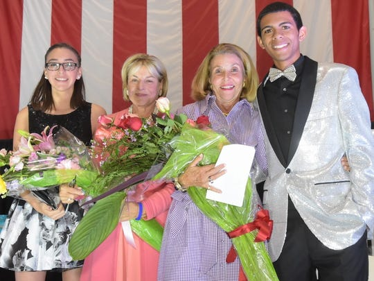 Angels Dinner co-hosts Kiara Lopez, left, and  Jaquan Pledger, right, thank event chairs Marcy DeWolfe and Nancy Lynch with bouquets of flowers.