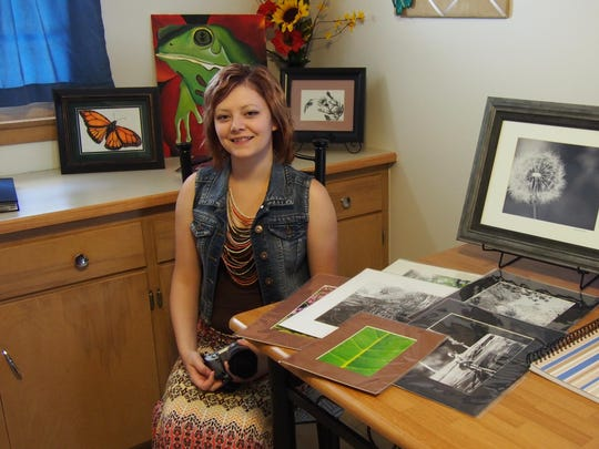 Sarah Ninnemann, of Fond du Lac, sits beside some of her paintings, drawings and photographs. Her favorite is a yet-unfinished painting of a frog, her favorite creature, which sits behind her.