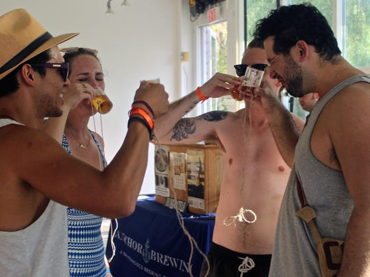 A group of friends taste different beer flavors crafted by the La Quinta Brewing Co., Saturday, during the craft beer weekend at the ACE Hotel in Palm Springs.