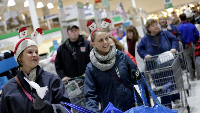 Collette Ridley, left, of Little Chute and Katie Chase of Greenville don Santa attire as they shop at Menards during Black Friday in Grand Chute.