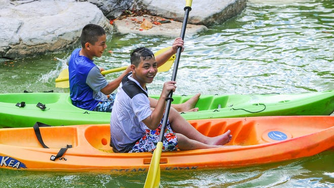 Wish kid Miguel Rosario, 12, front, and his twin brother, Michael, try their hand at paddling at the Pacific Islands Club Guam water park on Friday. A weekend stay at the Tumon hotel was a wish granted to him by the Make-A-Wish Foundation of Guam. Miguel Rosario was born with a heart defect and is awaiting valve implant surgery, said his mother, Annie Rosario. The boy originally wished for a family trip to Disney World in Florida, but revised his wish after doctors said he may not be able to handle the long trip, according to his mom.